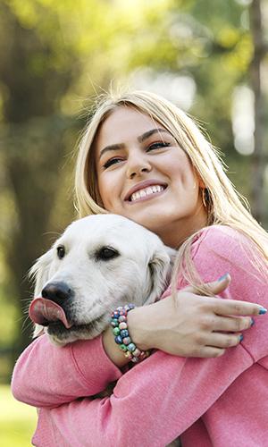 Responsible dog owner hugging her dog.